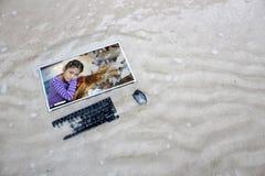 Ordinateur sur la plage avec la fille et les tortues de mer asiatiques sur l'écran Photographie stock