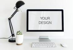Ordinateur sur la table blanche dans l'espace de travail avec la lampe noire et le petit p Photographie stock