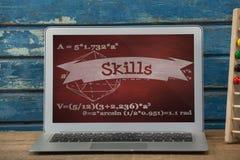 Ordinateur sur une table d'école avec des icônes d'école sur l'écran Images stock