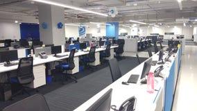 Ordinateurs et téléphones dans le poste de travail une société de technologie de l'information image libre de droits