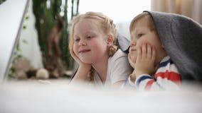 Ordinateurs pendant les vies des enfants modernes petit frère et bandes dessinées de observation de soeur sur l'ordinateur portab banque de vidéos