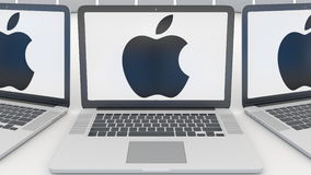 Ordinateurs portables avec Apple Inc logo sur l'écran Entrée moderne d'immeuble de bureaux Éditorial conceptuel 3D d'informatique Photos stock