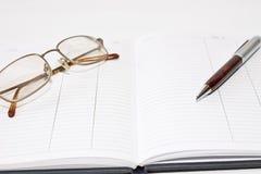 Ordine del giorno con la penna ed i vetri Fotografie Stock Libere da Diritti