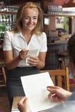 Ordine di In Restaurant Taking della cameriera di bar dal cliente immagine stock libera da diritti