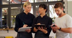 Ordine di scrittura della cameriera di bar e del cameriere in blocco note 4k video d archivio