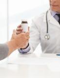 Ordinerade mediciner. Manipulera att ge en flaska av preventivpillerar till det passande Royaltyfri Fotografi