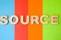 Ordkälla av stora träbokstäver på kulör bakgrund av 4 färger: blått apelsin, rött och grönt Bruk av ordkällan direktanslutet, in Royaltyfri Foto