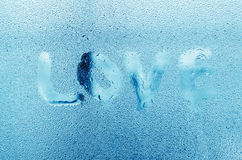 """Ord""""Love"""" med vatten tappar på det glass fönstret Royaltyfria Bilder"""