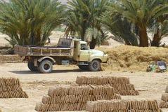 Ordna till för att ladda lastbilen som parkeras på gyttjategelstenfabriken i Shibam, Yemen Arkivbild