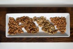 Ordnade pecannötter, valnötter och mandlar på det vita magasinet Royaltyfria Bilder
