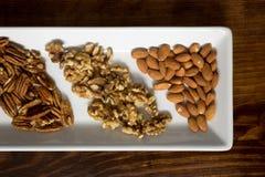 Ordnade pecannötter, valnötter och mandlar på det vita magasinet, slut Royaltyfri Fotografi