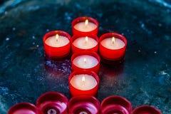 Ordnade röda stearinljus i ett kors Fotografering för Bildbyråer