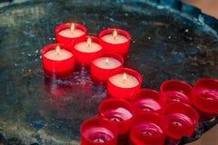 Ordnade röda stearinljus i ett kors Royaltyfria Bilder