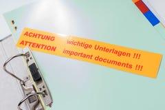Ordner mit Aufkleber - wichtige Dokumente der Aufmerksamkeit!!! - Englisch und Deutscher stockfoto