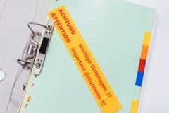 Ordner mit Aufkleber - wichtige Dokumente der Aufmerksamkeit!!! - Englisch und Deutscher lizenzfreies stockfoto