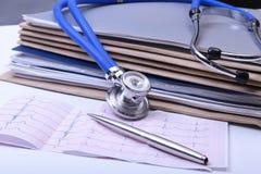 Ordnerdatei und -stethoskop auf dem Schreibtisch Stockbilder