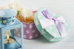 Ordning av blå lanter, blommor, pastellfärgad gåvaask Royaltyfri Foto