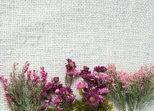 Ordning av konstgjorda blommor som lokaliseras på jutesäckvävbakgrund som är användbar som den easter bakgrund och vykortet Royaltyfria Bilder