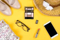 Ordning av nödvändig kvinnasommartillbehör på ljus gul bakgrund Arkivfoton