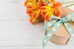 Ordning av orange liljablommor och gåvaasken Royaltyfria Bilder