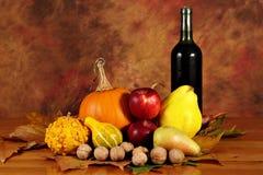 Ordning av pumpor, höstfrukter och vin Arkivfoto