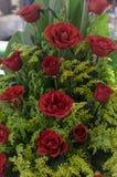 Ordning av rosor i en korg som förläggas i stånd arkivbild