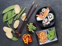 Ordning av sushi med pinnar, inlagda grönsaker och peppar Arkivbild