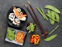 Ordning av sushi med pinnar, inlagda grönsaker och peppar Royaltyfri Foto