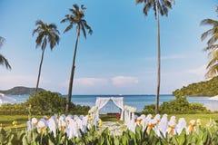 Ordning för mötesplats för strandbröllop i natur, blommagarnering med kokosnöten och hav i bakgrund arkivfoton