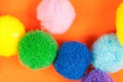 Ordningen av mjuka bollar för den livliga färgrika fluffiga luddiga textilen på den vibrerande apelsinen skyler över brister bakg Royaltyfri Bild