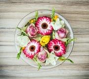 Ordningen med rosor och gerberas blommar i intelligensen för den glass bunken Royaltyfri Foto