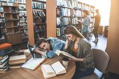 Ordningsamma studenter som läser volymer för studie fotografering för bildbyråer