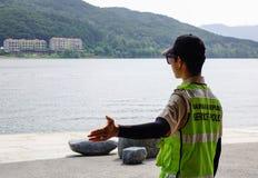 Ordningsvakt i likformign som står nära sjön royaltyfria bilder