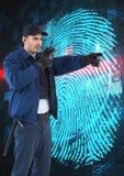 Ordningsvakt som använder radion, medan peka bort mot fingeravtryck på skärmen Arkivfoto