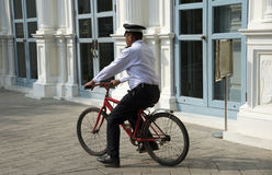 Ordningsvakt som rider en röd cirkulering arkivbild