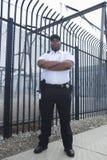 Ordningsvakt Standing In Front Of Prison Fence Arkivbild