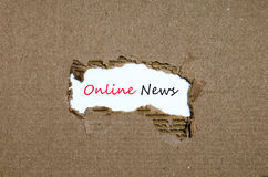 Ordonline-nyheterna som visas bak sönderrivet papper Arkivbilder