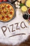 Ordpizza som är skriftlig i mjöl med olika ingredienser arkivfoto