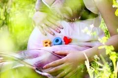 Ordpojke som är skriftlig med färgrika alfabetkuber på den gravida buken Arkivbild