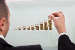 Ordre croissant de Stacking Coins In d'homme d'affaires Photographie stock