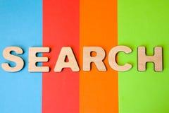Ordsökande av stora träbokstäver på kulör bakgrund av 4 färger: blått apelsin, rött och grönt Bruk av ordsökandet i online-s Royaltyfri Fotografi