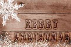 Ords Merry Christmas written, burned letters on wooden snowy brown backgroun Stock Photos