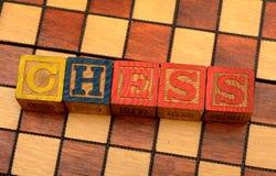 Ordschack på schackbrädebakgrund arkivbilder