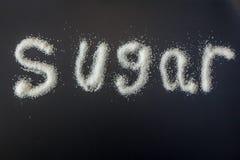 Ordsockret som är skriftligt i vita förädlade grans av socker fotografering för bildbyråer