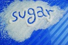 Ordsockret som skrivs mot socker på bluen Royaltyfri Foto