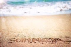 Ordsommar på sand av havsstranden Arkivbild