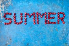 Ordsommar som göras av körsbär på texturerad blå bakgrund Arkivbild