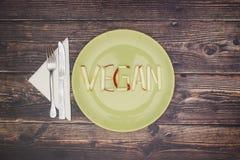 Ordstrikt vegetarian på grön maträtt arkivfoto