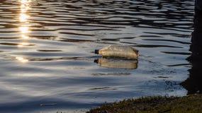 Ordures en plastique de bouteille d'eau flottant dans le lac au coucher du soleil image libre de droits