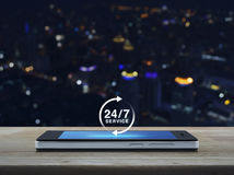 24 ore assistono l'icona sullo schermo moderno dello Smart Phone sulla linguetta di legno Immagini Stock Libere da Diritti